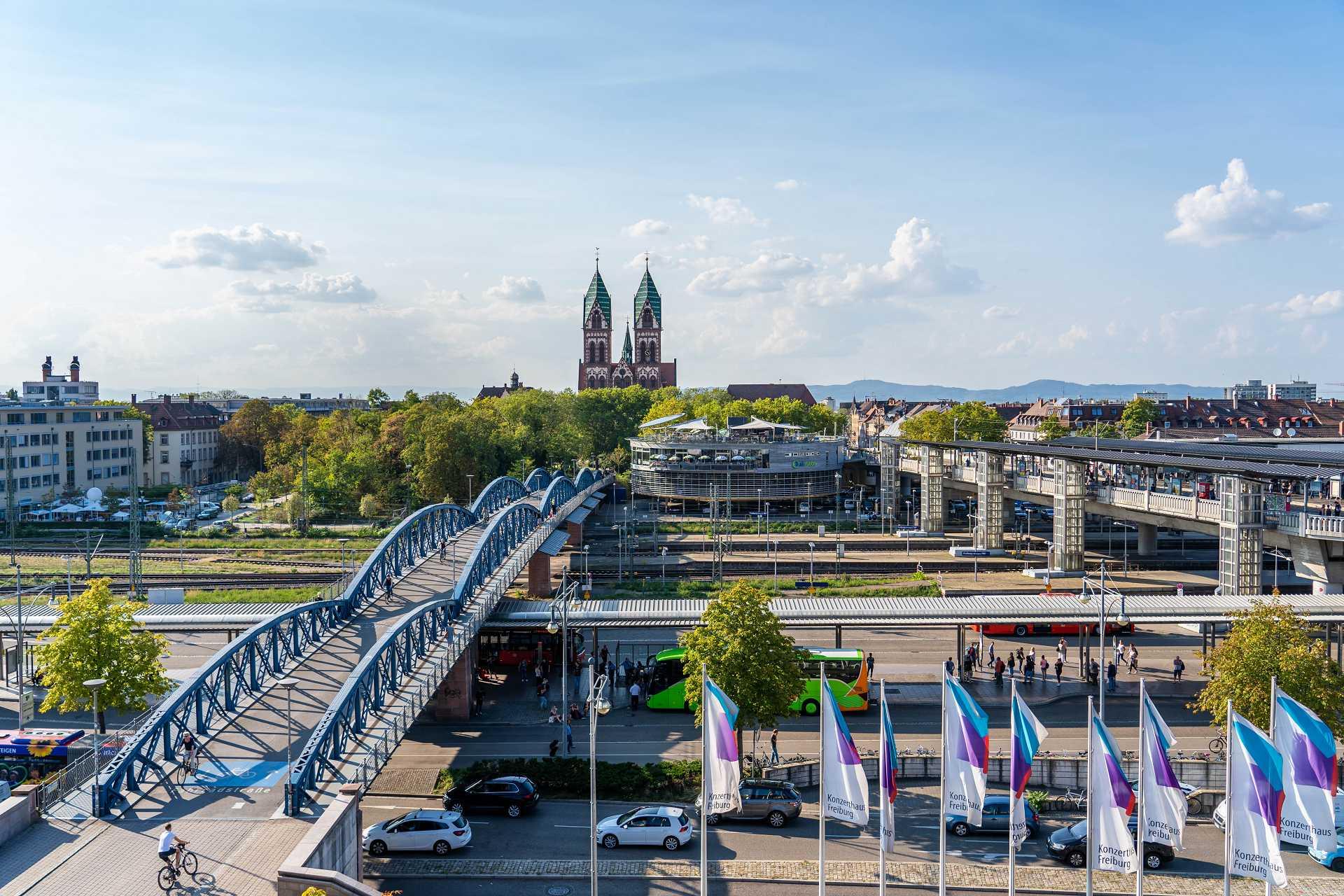 Blick auf Wiwílibrücke, Herz-Jesu-Kirche und Hauptbahnhof mit wehenden Fahnen in Freiburg | Kongressstadt Freiburg