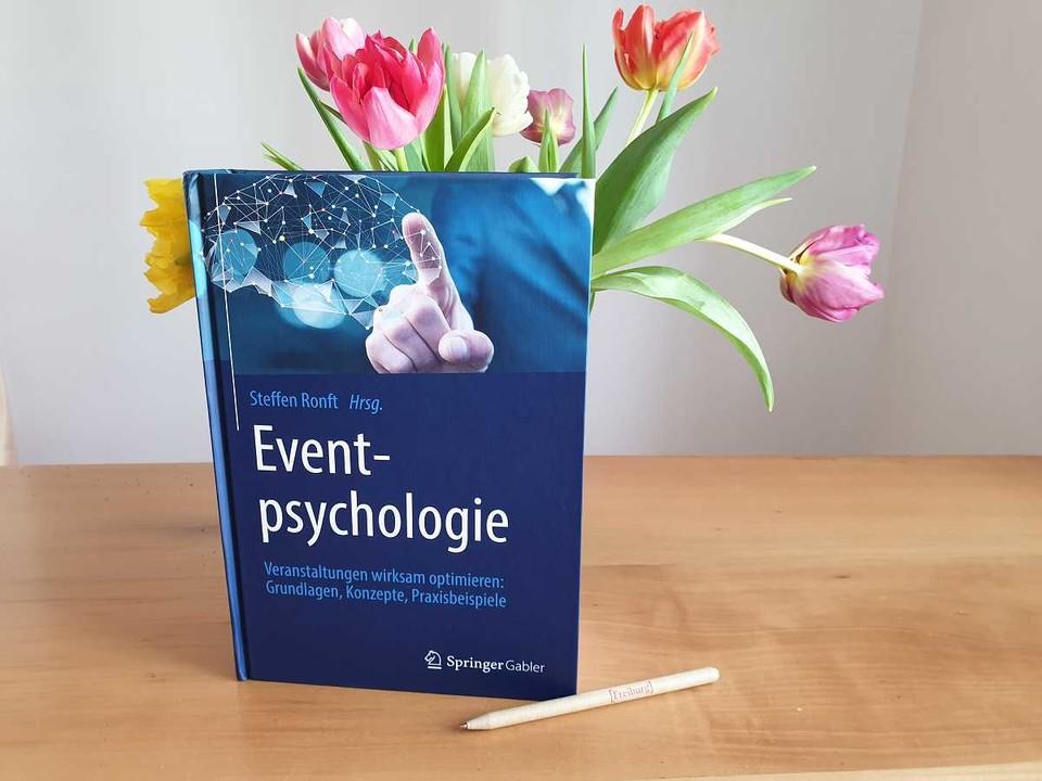 Buch Eventpsychologie neben Vase mit Tulpen